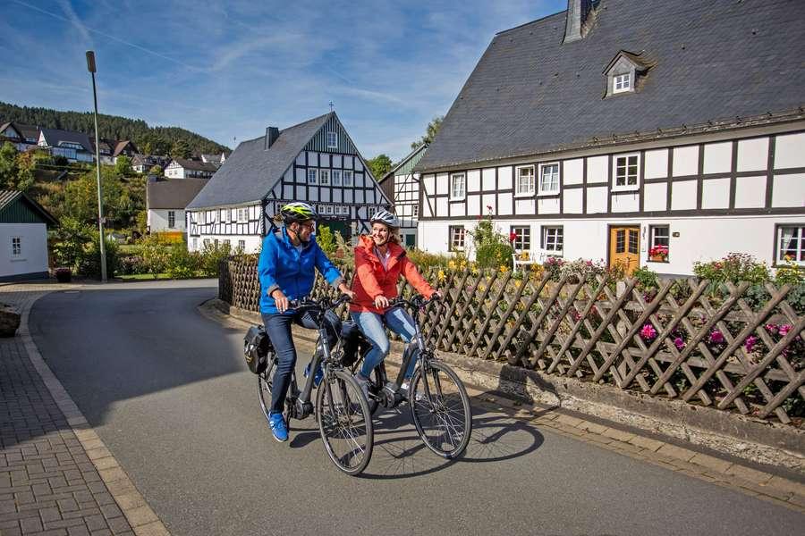 Paar fährt auf Fahrrad durch Fachwerkhaüser