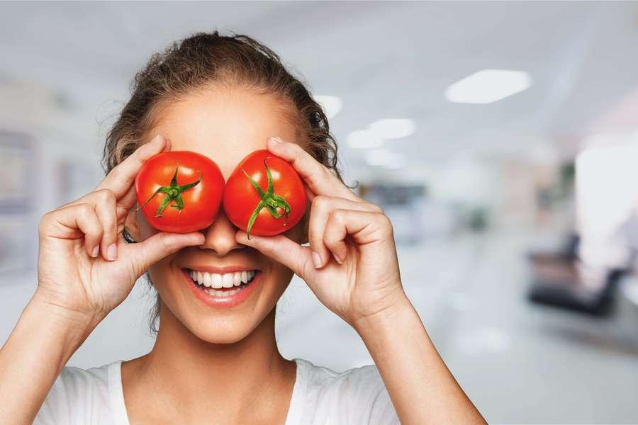 Frau hält sich Tomaten vor die Augen