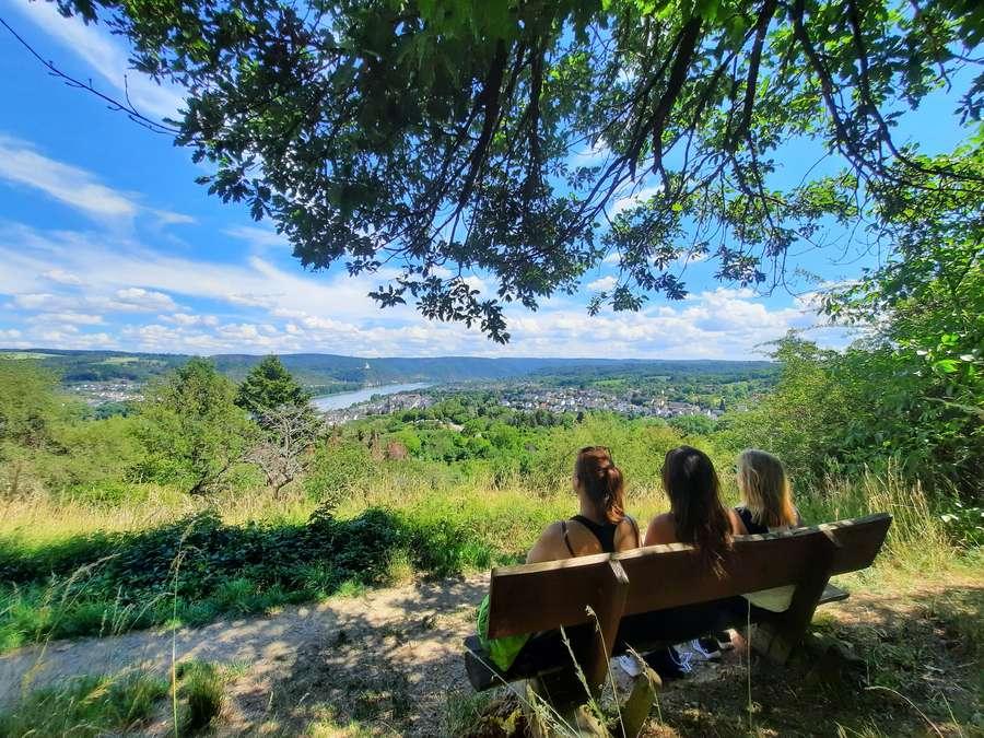 Gruppe sitzt auf Bank und schaut ins Rheintal