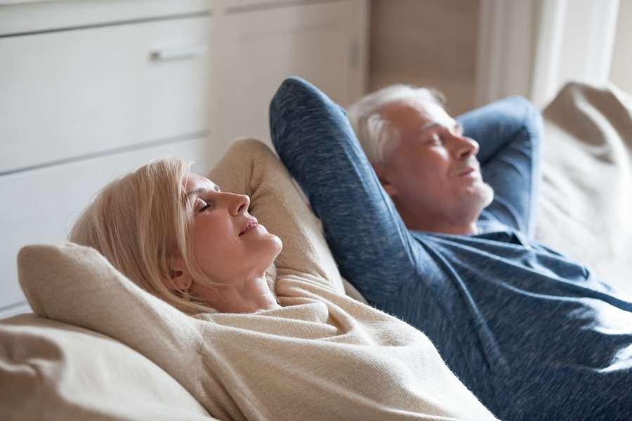 Seniorenpaariegt entspannt auf dem Rücken