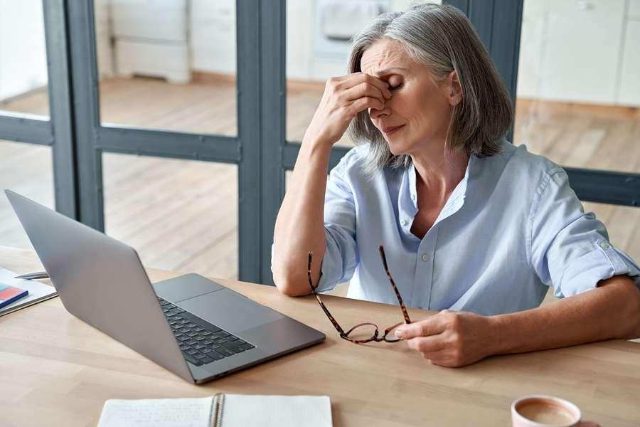 Frau sitzt erschöpft vor Laptop