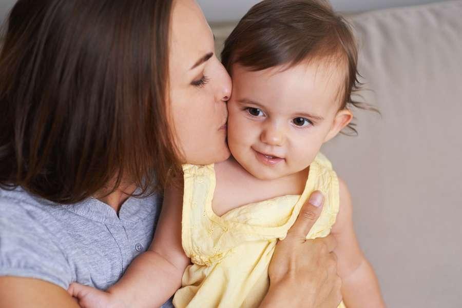 Mutter küsst ihr Babay beim Abtrocknen