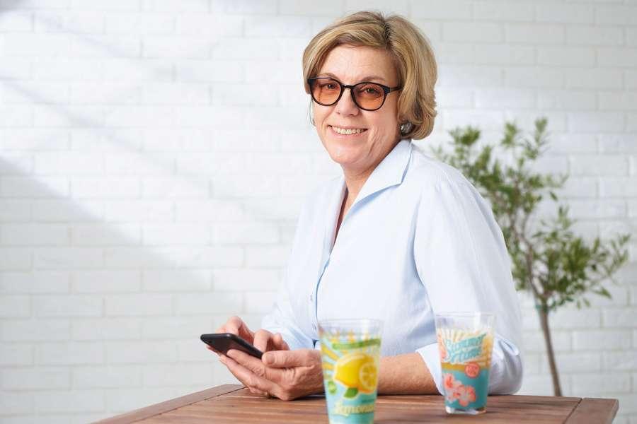 Frau sitzt am Tisch mit Smartphone