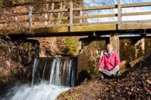 Frau meditiert an Bachlauf mit Brücke