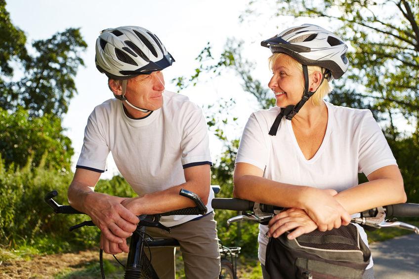 Seniorenpaar steht mit Fahrrad und schaut sich an