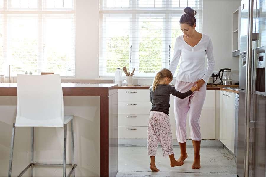Mutter tanzt mit Tochter in Küche