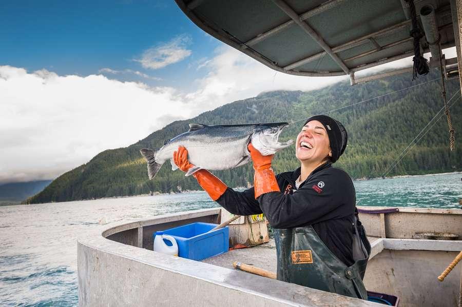 Frau auf Boot mit Lachs in der Hand