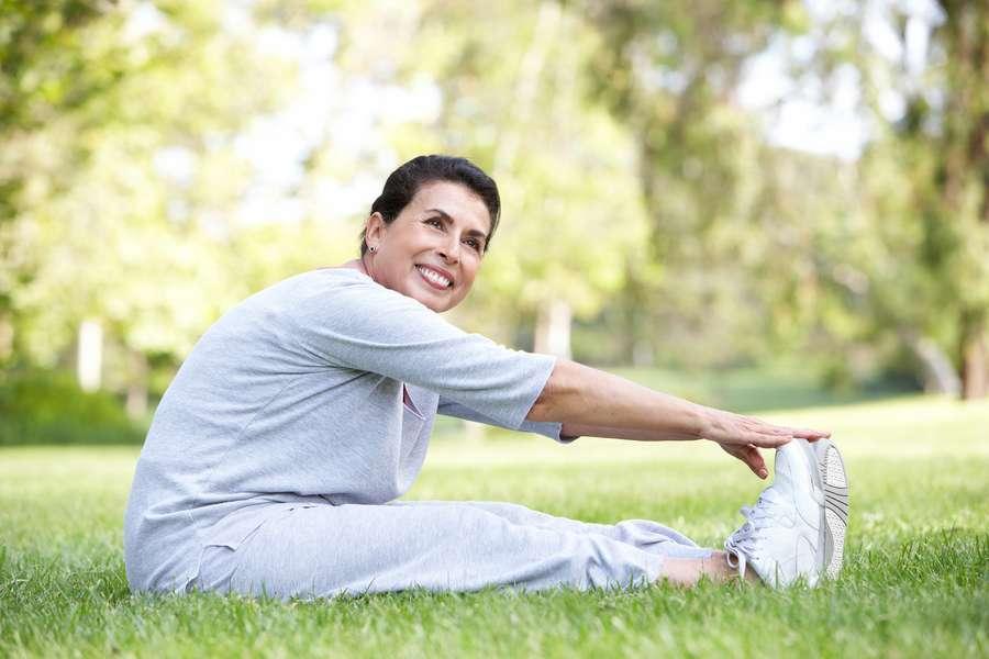 Junge Frau beim stretchen im Park