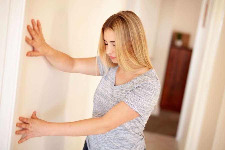 Frau hält sich an Wand wegen Schwindel fest.